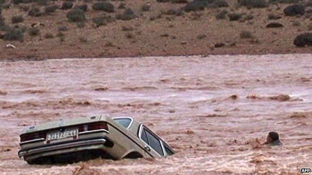 A driver and his car are stranded in flood waters on 23 November 2014 in the southern region of Ouarzazate in Morocco