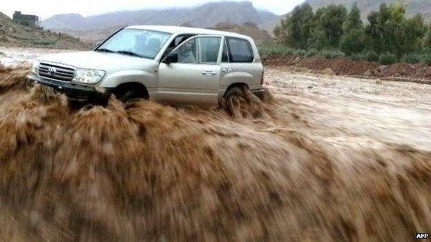 A driver and his car are stranded in flood waters on 23 November 2014 in the southern region of Ouarzazate in Morocco.
