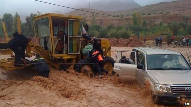 Firemen rescue a driver trapped in flood waters on 23 November 2014 in the southern region of Ouarzazate in Morocco.
