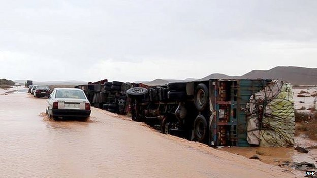 Cars move slowly through muddied flood waters beside overturned trucks on 23 November 2014 in the southern region of Ouarzazate in Morocco