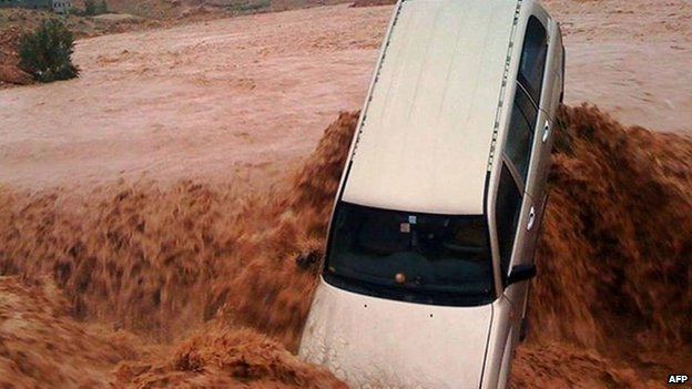 A car is carried away by flood waters on 23 November 2014 in the southern region of Ouarzazate in Morocco