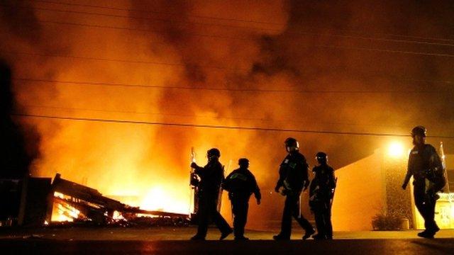 Police in riot gear walk past a burning building in Ferguson, Missouri