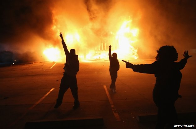 Demonstrators celebrate as a business burns in Ferguson, 24 November