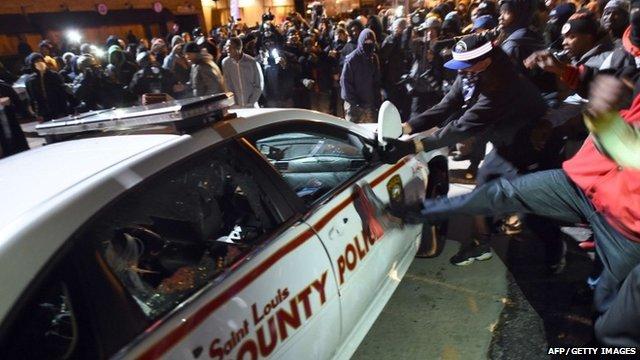 Protesters attack a police car