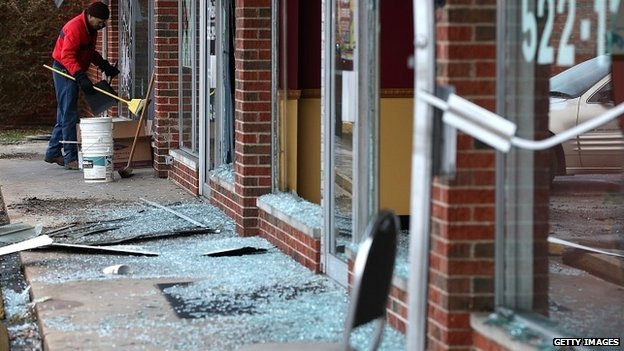 A worker cleans up glass at a building damaged during riots in Dellwood, Missouri - 25 November 2014
