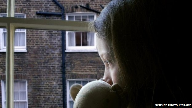 Anonymous child looking out of a window holding a teddy bear