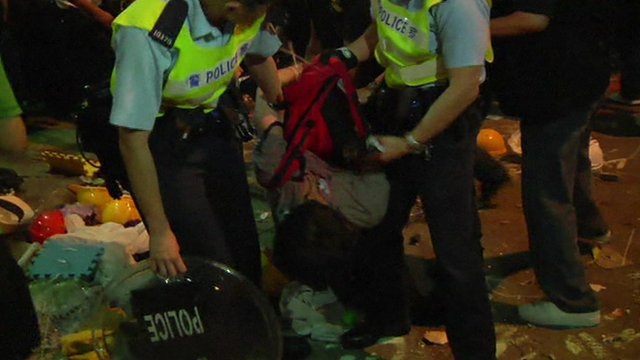 Two police officers remove a protester