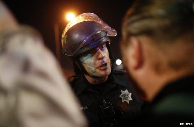A policeman confronts a protester in Oakland, California, 25 November