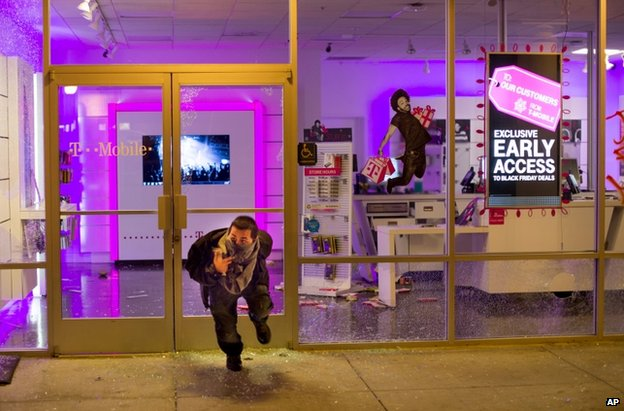 A man leaves a looted mobile phone shop in Oakland, 25 November