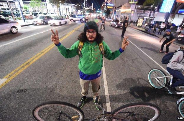 A cyclist blocks a road in Los Angeles, 25 November