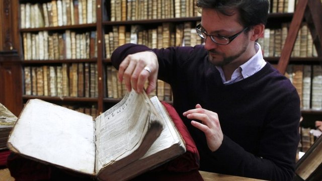 "Remy Cordonnier, the director of the Saint-Omer library's medieval and early modern collection, opens a page of the newly discovered Shakespeare""s original first folio."