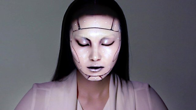 A model with a projection mapped onto her face