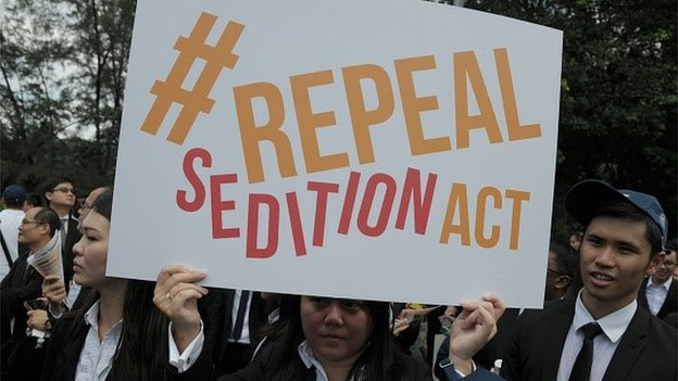 In a photo taken on October 16, 2014, a Malaysian Lawyer holding a placard outside the Parliament house during a rally to repeal the Sedition Act in Kuala Lumpur.