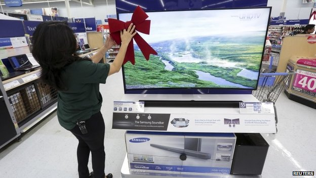 An employee adjusts a large ribbon on a television display at Wal-Mart as the store prepares for Black Friday in Los Angeles, California November 24, 2014