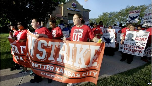 """Protesters march outside a Taco Bell restaurant in Kansas City, Mo. on Thursday, Sept. 4, 2014, as part of the """"Fight for $15"""" campaign, a national protest to push fast-food chains to pay their employees at least $15 an hour"""