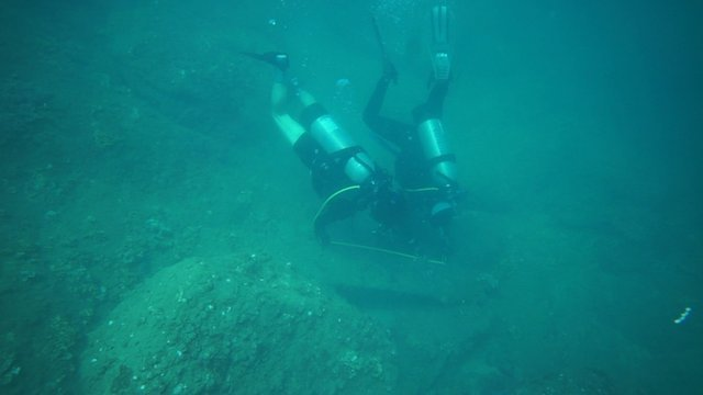 Divers examining what could be part of a medieval Chinese anchor