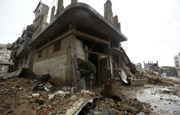 a Palestinian man, collects wood for a fire outside his destroyed home in Gaza City's Shejaiya neighbourhood on 24 November 2014