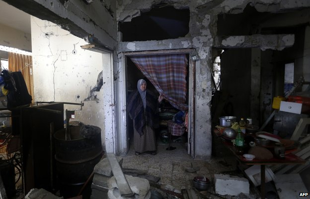 Palestinian woman stands in her destroyed home where she lives with her family on a rainy day in Gaza City's Shejaiya neighbourhood on 24 November 2014