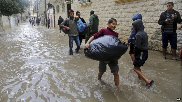 Palestinians carry their belongings as they leave their flooded family house during heavy rain in Gaza City, northern Gaza Strip, 27 November 2014