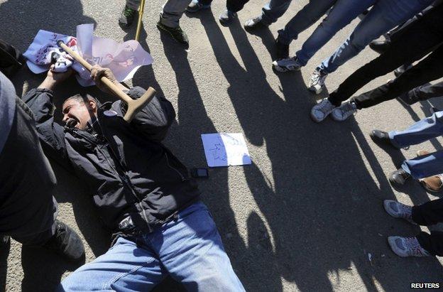 An anti-Mubarak demonstrator reacts to the verdict outside the Cairo court, 29 November