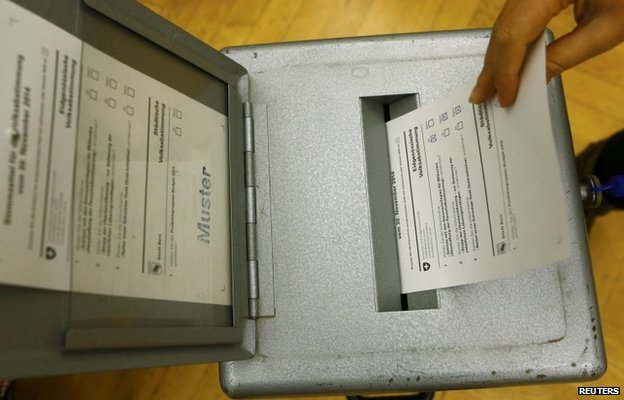 A man casts a ballot in Bern, Switzerland, on 29 November 2014