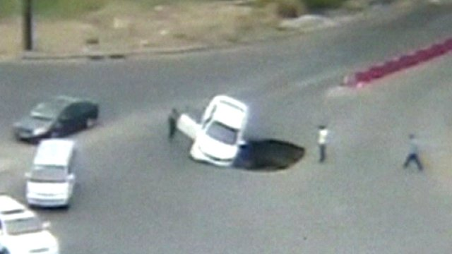 Car being swallowed by sinkhole