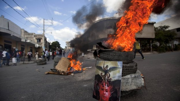 Image of Haiti's Prime Minister Laurent Lamothe stands against burning tyres in Port-au-Prince. 5 Dec 2014