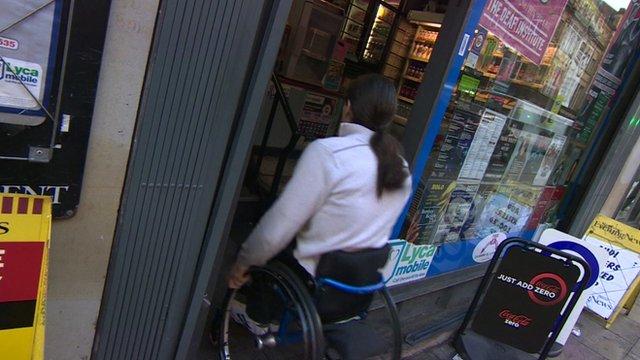 Man in wheelchair entering shop