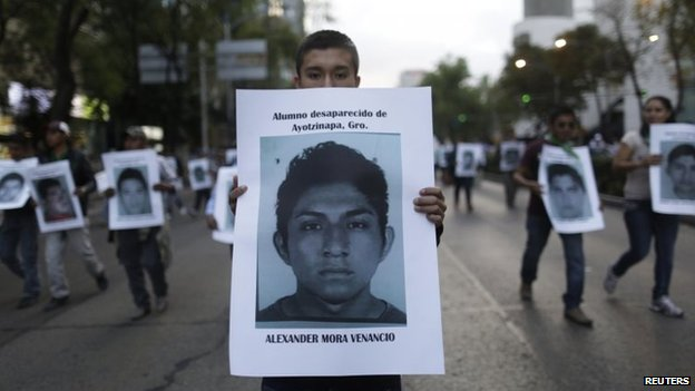 A demonstrator carries a photograph of Alexander Mora Venancio in Mexico City on 6 December December, 2014