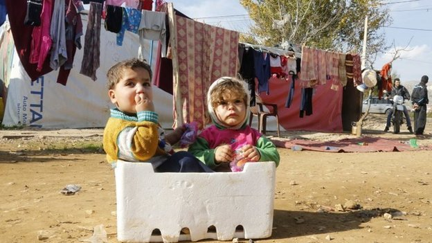 Syrian refugee children sit in a box at a makeshift settlement in Qab Elias in the Bekaa valley