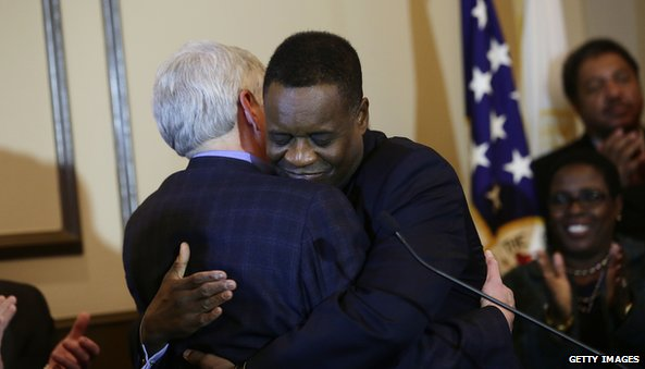 Emergency Manager Kevyn Orr (R), receives a hug from Michigan Governor Rick Snyder (L)
