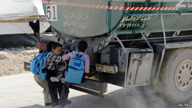 Syrian children hitch a ride from the back of a water tanker at the Al Zaatari refugee camp in the Jordanian city of Mafraq (7 December 2014)
