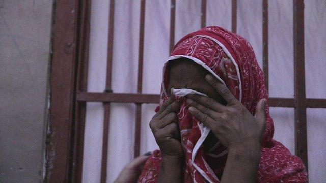 A woman covers her face as she cries