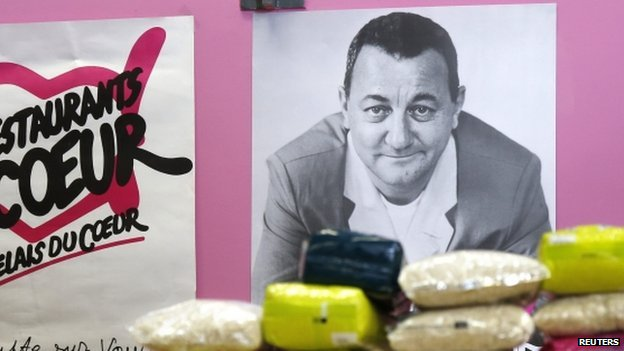 """Packages of rice are displayed in front of a picture of late French comic Coluche at a food distribution centre for the """"Les Restos du Coeur"""" (Restaurants of the Heart) in Paris on 24 November 2014."""