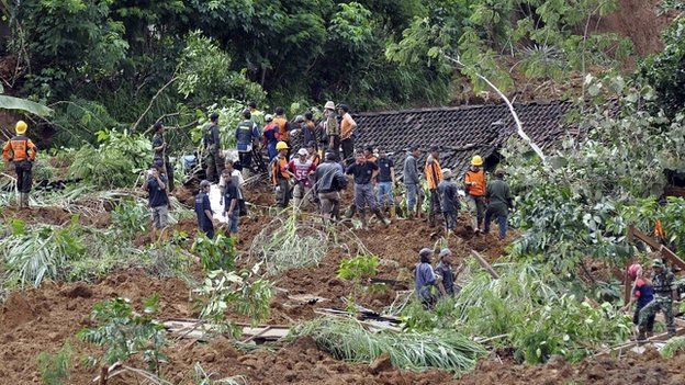 Rescue workers stand near houses buried in the mud after a landslide hit the village of Sampang in Banjarnegara - 13 December 2014