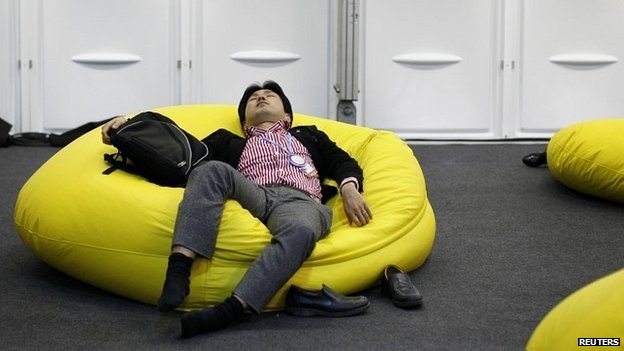 A delegate rests during a break at the UN climate change talks in Lima - 13 December 2014