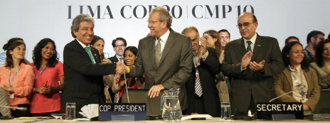 Peruvian environment minister Manuel Pulgar-Vidal shakes hands with his colleagues after sealing an agreement in Lima - 13 December 2014