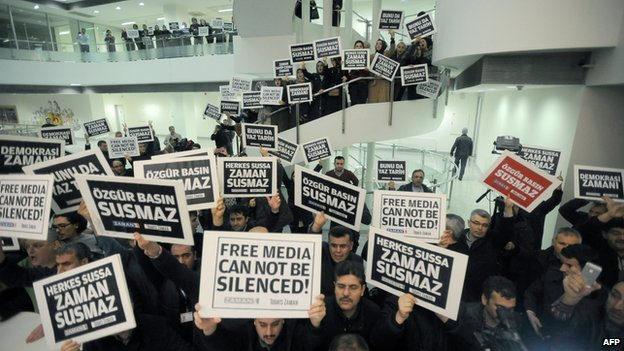 Zaman journalists hold banners inside the newspaper's headquarters in Istanbul.
