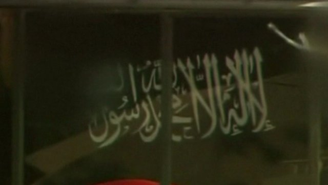 """A black flag bearing the white Arabic text of the """"shahada"""", the basic statement of the Islamic faith, being held in the Lindt Chocolat Cafe, Sydney, 15 December 2012"""
