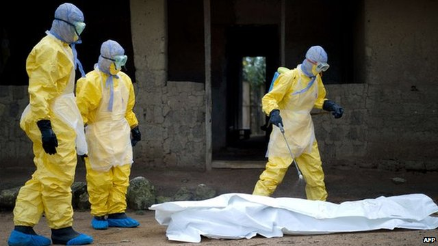 Red Cross workers in Guinea prepare to carry body of ebola victim.