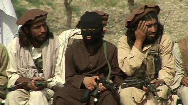 Taliban members sitting with guns