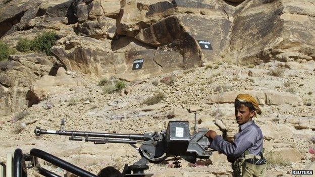 Shia Houthi rebel patrols through Radaa in central Yemen, past cliffs painted with the flag of Ansar al-Sharia, an al-Qaeda affiliate (23 November 2014)