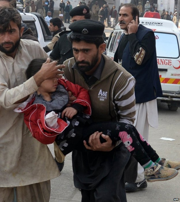An injured girl is carried to hospital in Peshawar, 16 December