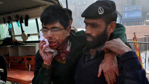 A man helps an injured student following a mass shooting in Peshawar - 16 December 2014