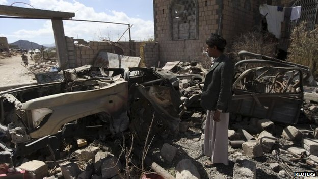 A Houthi rebel fighters inspects the wreckage of a car used in a suicide bomb attack in Radaa on 22 November 2014