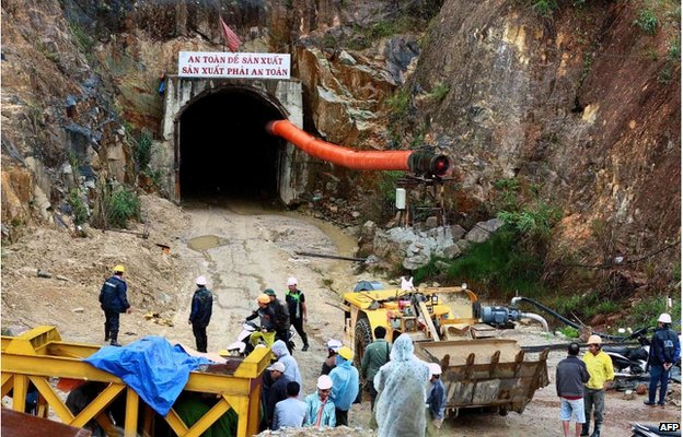 Workers and rescuers stand in front of the entrance of a tunnel at the Da Dang- Da Chomo hydroelectric power plant in Lac Duong district, central highland province of Lam Dong on 16 December 2014