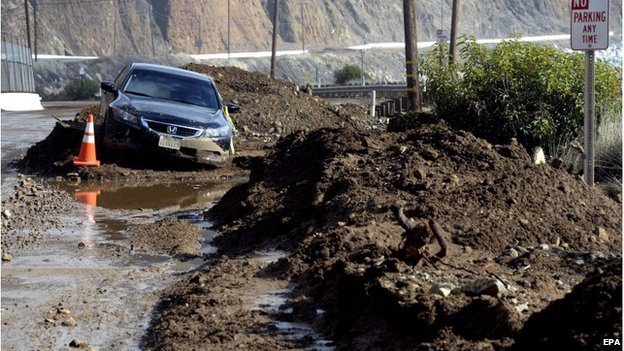 A car is trapped in a mud slide that closed a 10-mile portion of the Pacific Coast Highway, near Point Mugu, California