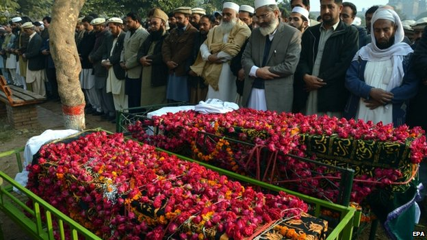 Funeral prayers of two school boys who were killed by Taliban militants at a school run by the Army, in Peshawar, Pakistan, 17 December 2014.