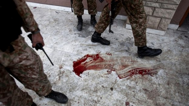 Pakistan army soldiers stand outside the auditorium of a school that was attacked by Taliban militants in Peshawar, Pakistan - 17 December 2014