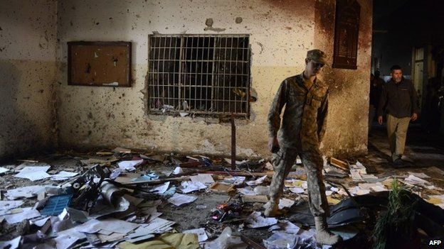 A Pakistani soldier walks amidst the debris in an army-run school a day after an attack by Taliban militants in Peshawar - 17 December 2014